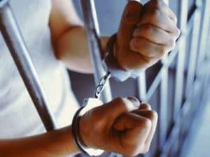 hands behind bars in cuffs